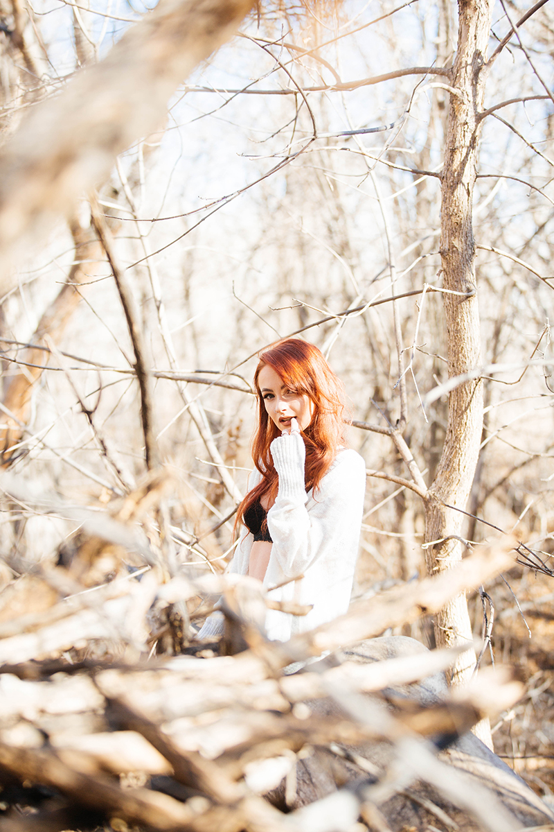 A beautiful young red head woman poses for a Bear Creek Nature Center boudoir photography session in Colorado Springs wearing a black bra, black underwear and a white sweater sitting on a fallen tree in a forested area