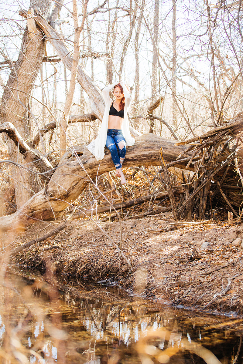 A beautiful young red head woman poses for a Bear Creek Nature Center boudoir photography session in Colorado Springs wearing a black bra, blue jeans and a white sweater sitting on a fallen tree in a forested area