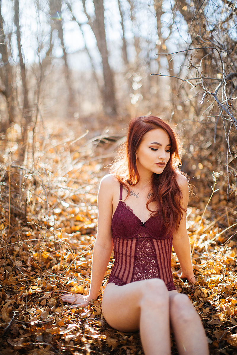 A beautiful young red head woman poses for a Bear Creek Nature Center boudoir photography session in Colorado Springs wearing red lingerie while sitting on the side of a hill covered in fall colors