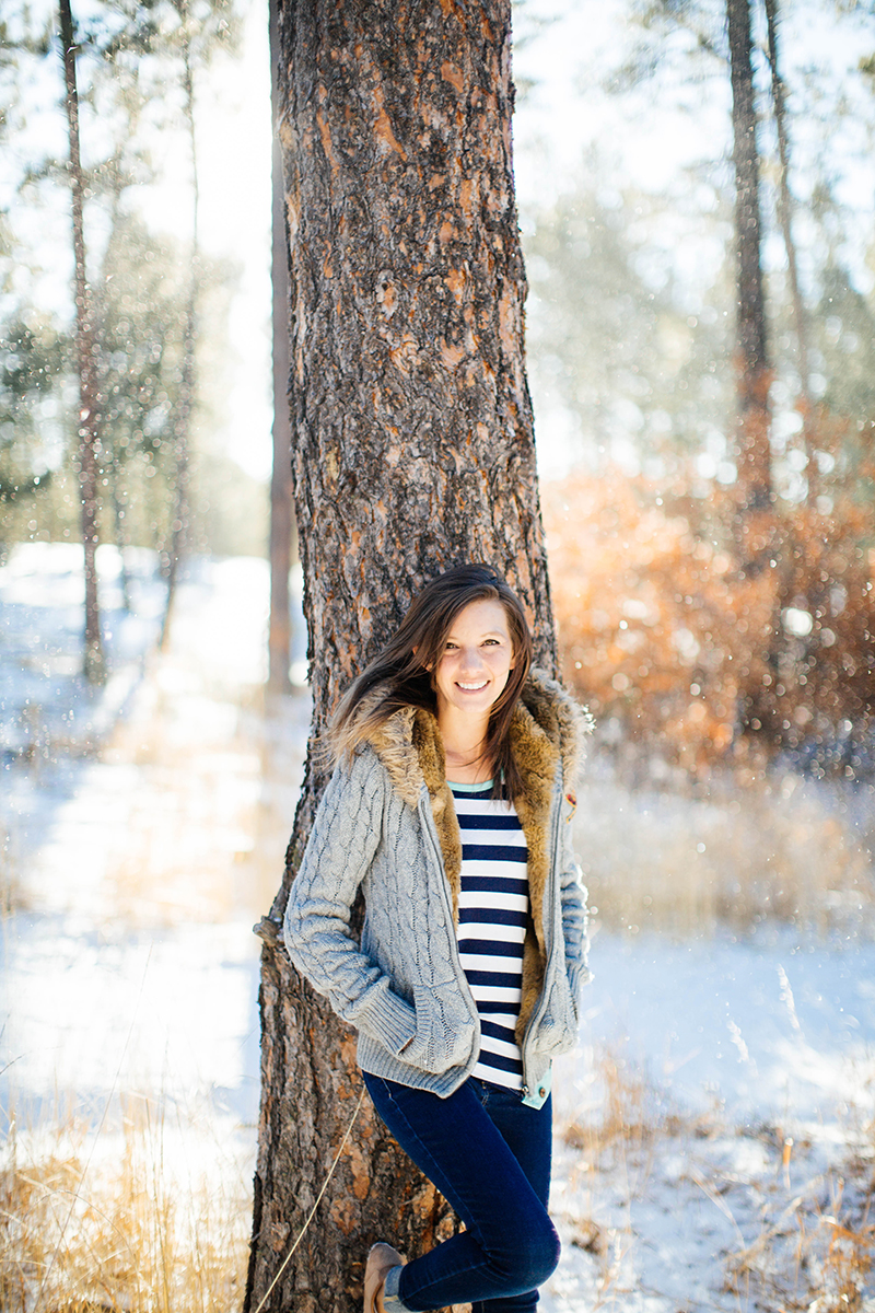 A beautiful brunette woman poses for a Fox Run Regional Park boudoir photography session in Colorado Springs, CO near Black Forest wearing a blue and white striped shirt, jeans and a gray hoodie with a fur hood leaning against a tree in a snow covered field