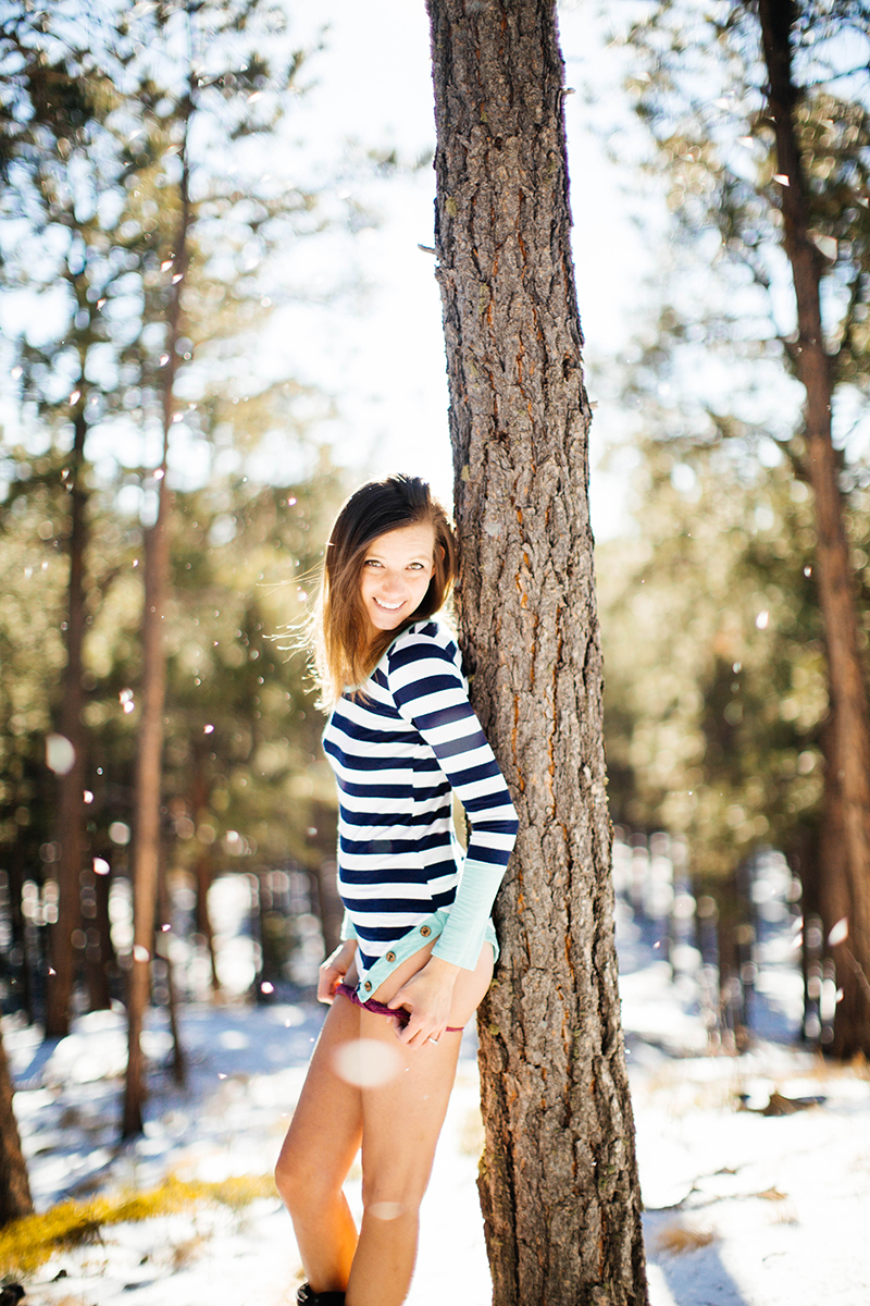 A beautiful brunette woman poses for a Fox Run Regional Park boudoir photography session in Colorado Springs, CO near Black Forest wearing a blue and white striped shirt pulling down her red underwear leaning against a tree as snow falls around her in a snow covered field