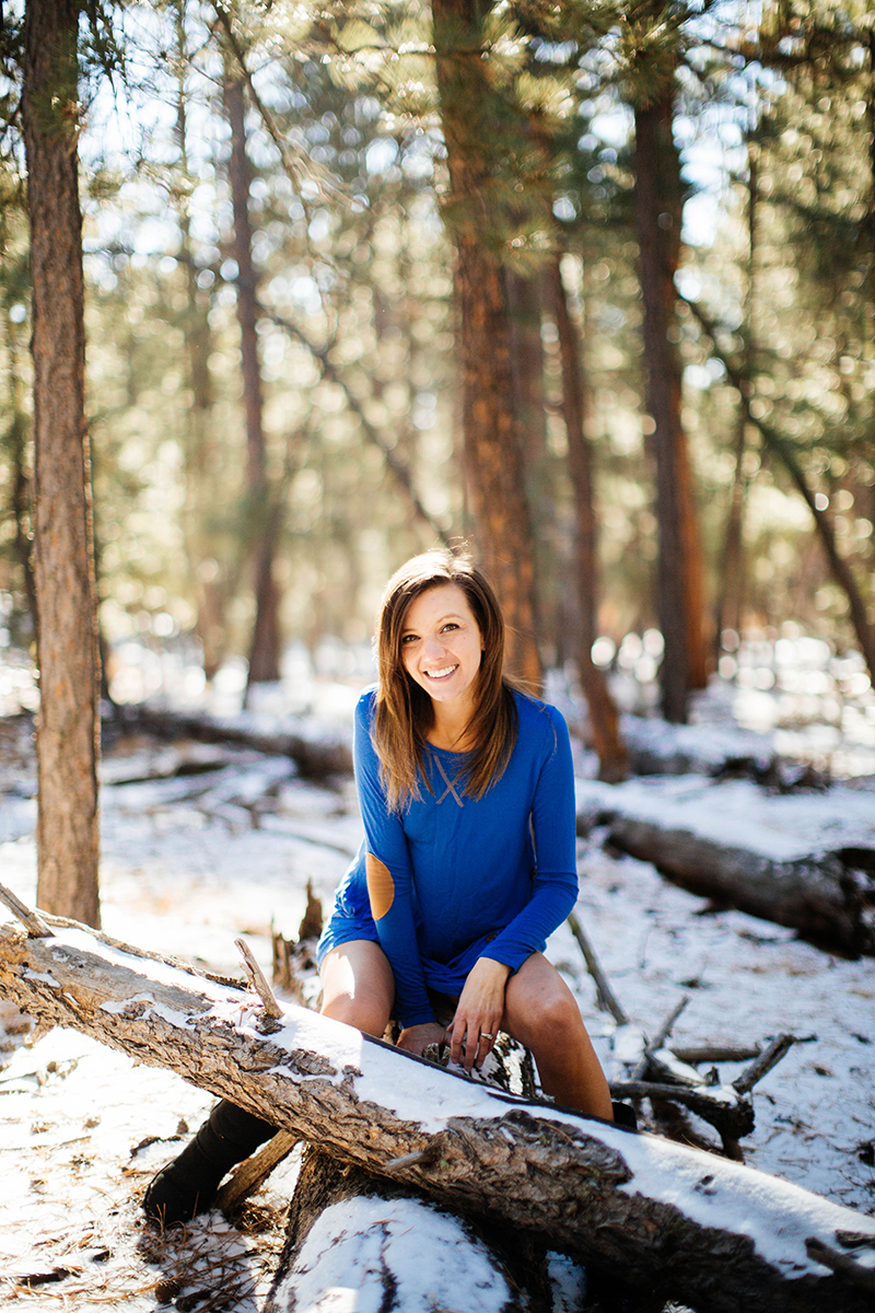 A beautiful brunette woman poses for a Fox Run Regional Park boudoir photography session in Colorado Springs, CO near Black Forest wearing a blue dress sitting on a fallen log in a field covered in snow