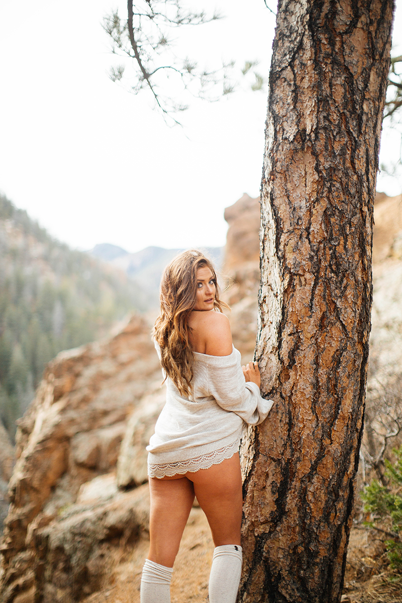 A beautiful brunette woman poses for a North Cheyenne Cañon Park boudoir photography session in Colorado Springs on a mountain top wearing a tan sweater and white knee high socks while leaning on a tree with mountains behind her