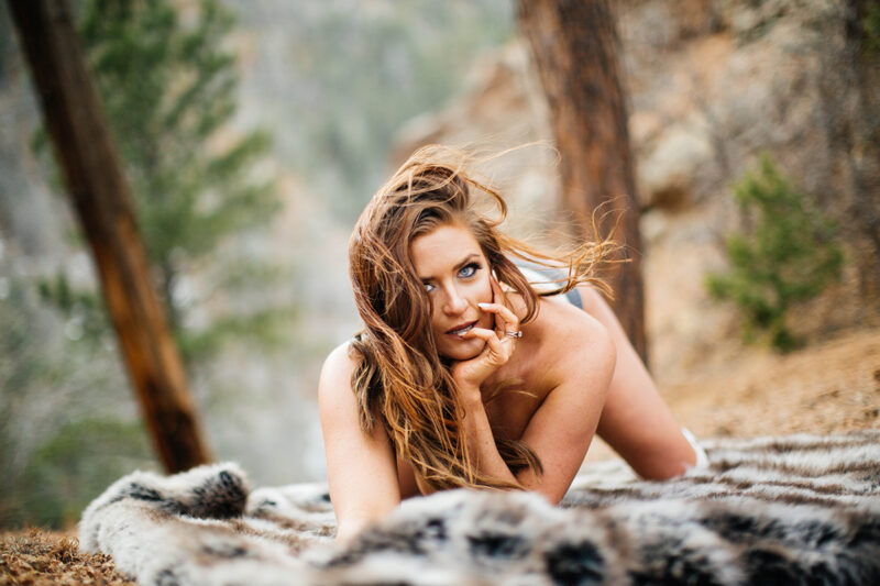 A beautiful brunette woman poses topless for a North Cheyenne Cañon Park boudoir photography session in Colorado Springs on a mountain top wearing gray underwear and white knee high socks while laying on a fur blanket with mountains behind her