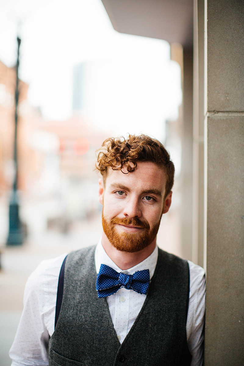 A handsome redhead male model poses for this downtown Denver fashion photography session in Colorado near Union Station wearing a white button up shirt, a gray vest, jeans and a blue bow tie leaning against a pillar on a street