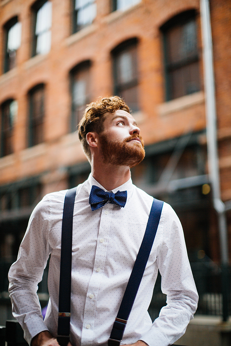 A handsome redhead male model poses for this downtown Denver fashion photography session in Colorado near Union Station wearing a white button up shirt, blue jeans, suspenders and a blue bow tie leaning against railing in an alley with a brick building in the background