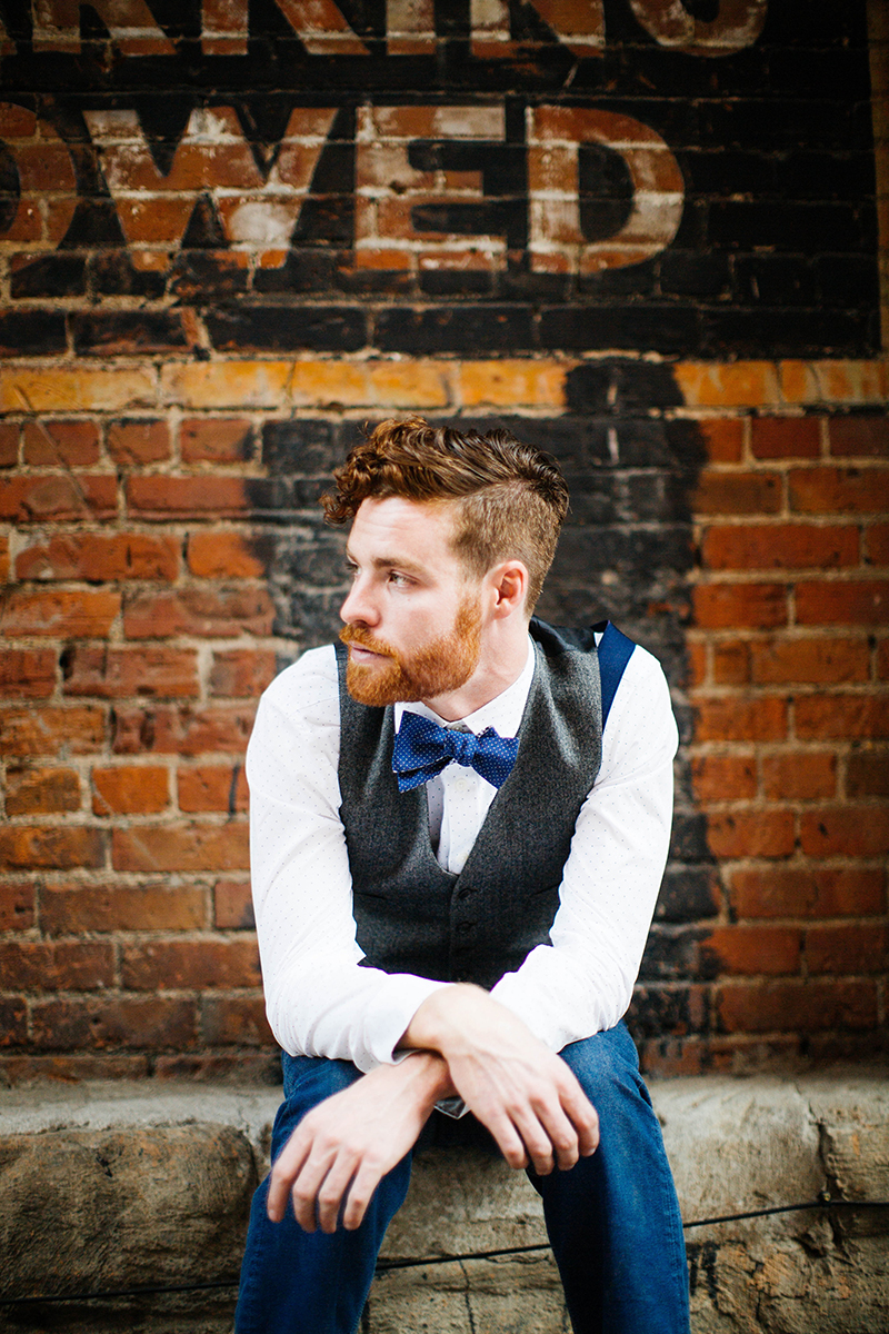 A handsome redhead male model poses for this downtown Denver fashion photography session in Colorado near Union Station wearing a white button up shirt, a gray vest, jeans and a blue bow tie sitting in a street against a brick wall
