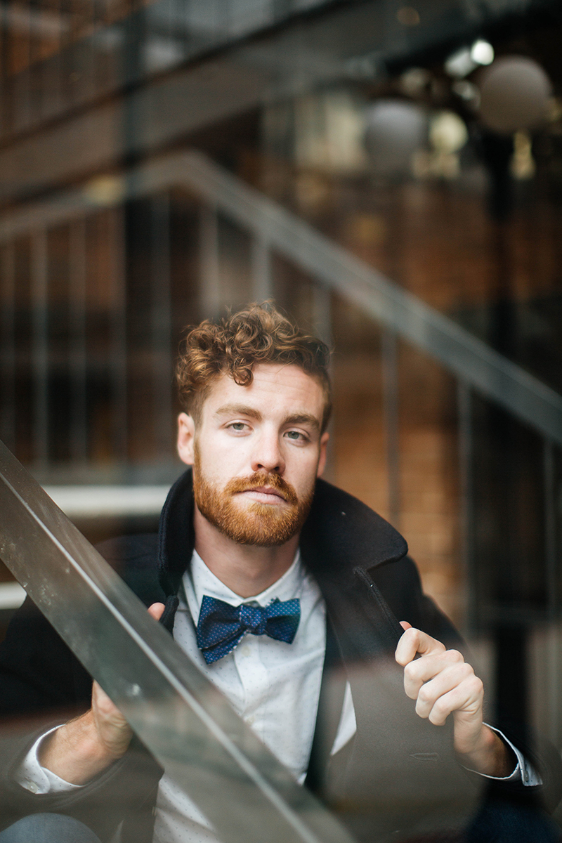 A handsome redhead male model poses for this downtown Denver fashion photography session in Colorado near Union Station wearing a white button up shirt, blue jeans, a black peacoat and a blue bow tie sitting on the stairs of a brick office building