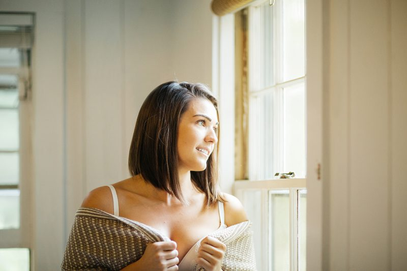 A beautiful young brunette woman poses for a Gloucester boudoir photography session near Boston, Massachusetts wearing a white bra and a tan sweater next to a window in a cottage