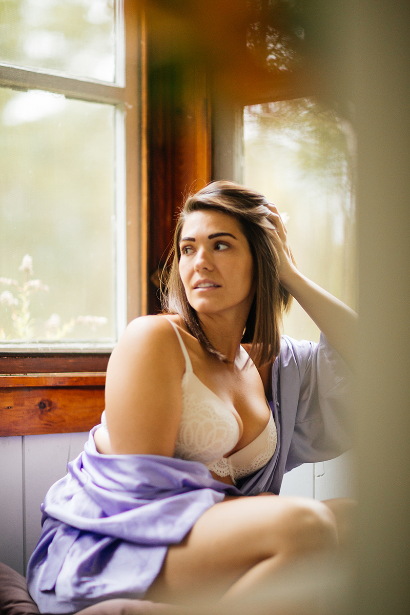A beautiful young brunette woman poses for a Gloucester boudoir photography session near Boston, Massachusetts wearing a white bra and a purple robe next to a window in a cottage