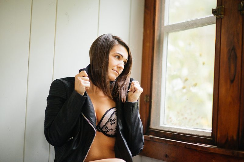 A beautiful young brunette woman poses for a Gloucester boudoir photography session near Boston, Massachusetts wearing a black and white bra with a black leather jacket next to a window in a cottage
