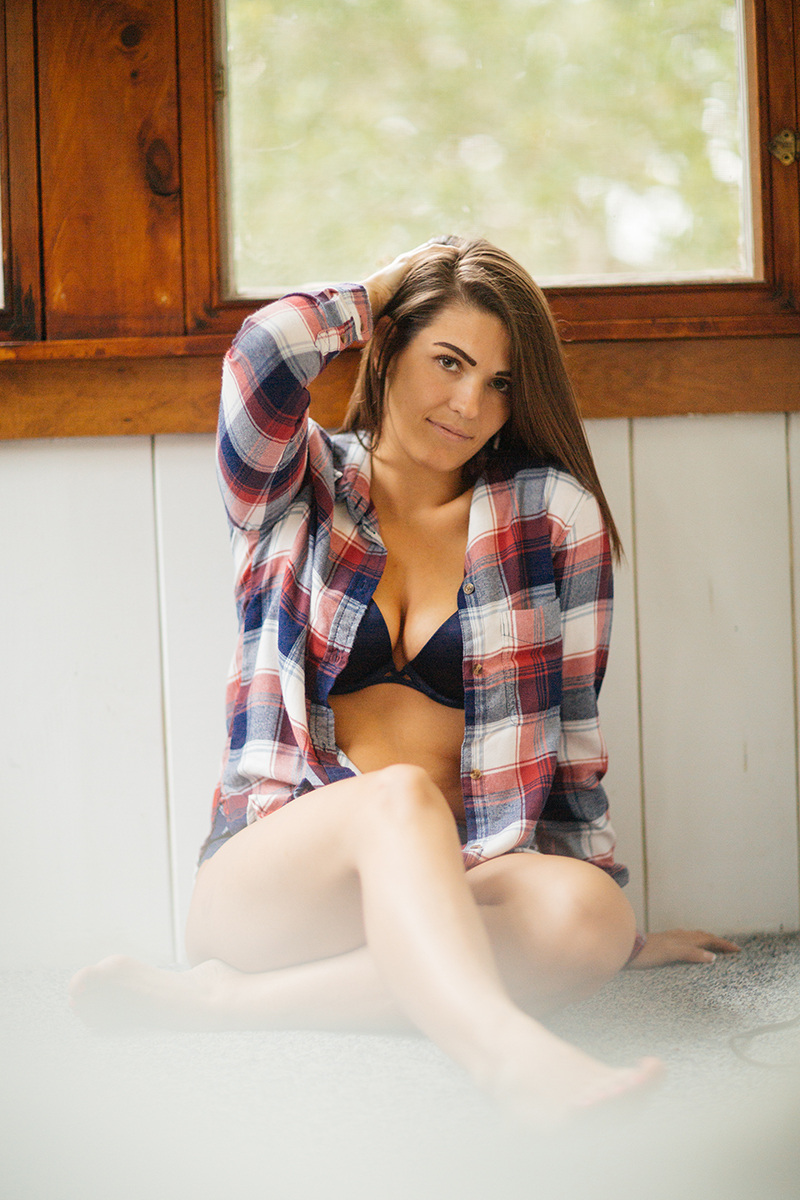 A beautiful young brunette woman poses for a Gloucester boudoir photography session near Boston, Massachusetts wearing a back bra with a red and blue plaid button up shirt next to a window in a cottage