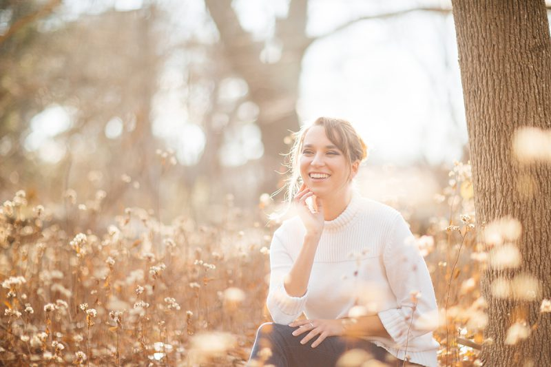 A beautiful young blonde woman poses for a Gloucester boudoir photography session near Boston, Massachusetts wearing a white sweater and blue jeans in a dry field near a cottage