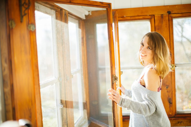 A beautiful young blonde woman poses for a Gloucester boudoir photography session near Boston, Massachusetts wearing a purple bra and gray sweater holding windows of a cottage open