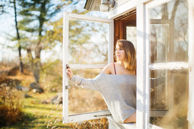 A beautiful young blonde woman poses for a Gloucester boudoir photography session near Boston, Massachusetts wearing a purple bra and gray sweater sitting in a window of a cottage