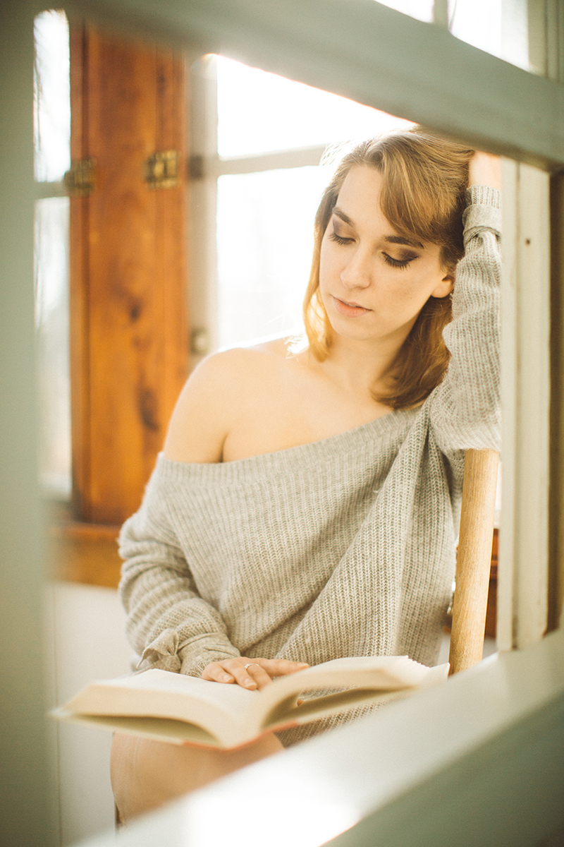 A beautiful young blonde woman poses for a Gloucester boudoir photography session near Boston, Massachusetts wearing a gray sweater sitting in a chair reading a book inside a cottage