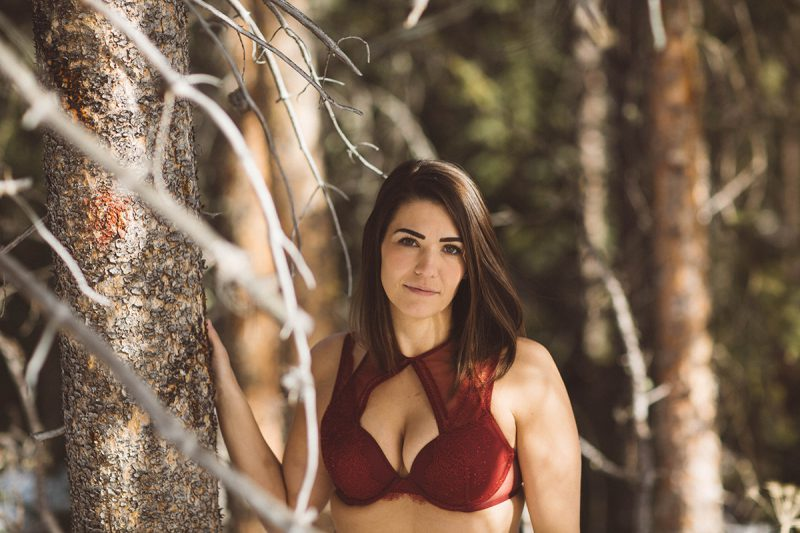 A beautiful young brunette woman poses for a Silverthorne condo boudoir photography session near Denver, Colorado wearing a red bra in a forest covered in snow