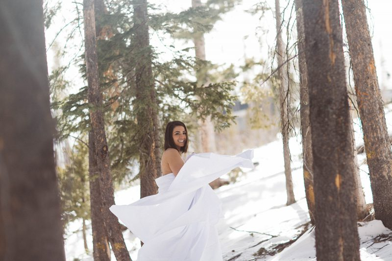 A beautiful young brunette woman poses topless for a Silverthorne condo boudoir photography session near Denver, Colorado wrapped up in a white bed sheet in a forest covered in snow