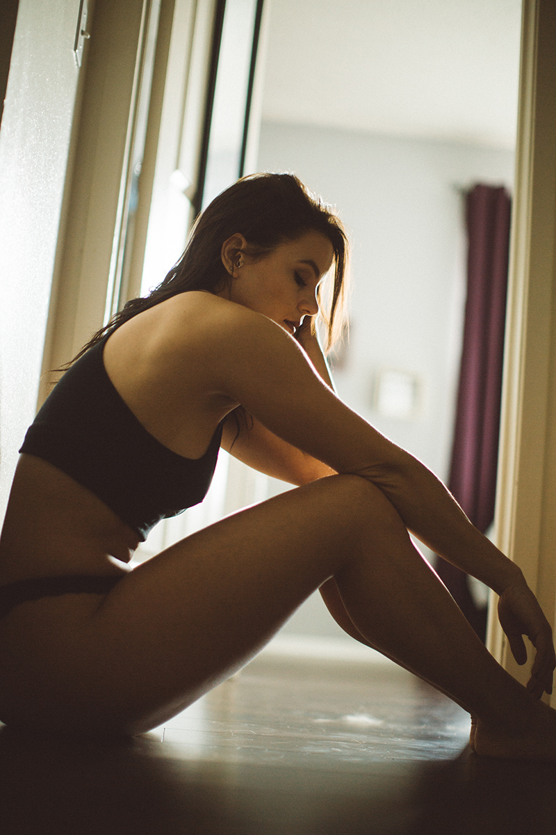 A beautiful young brunette woman poses for some Denver boudoir studio photos at a home studio in Thornton, Colorado wearing a black sports bra and black underwear sitting in a hall