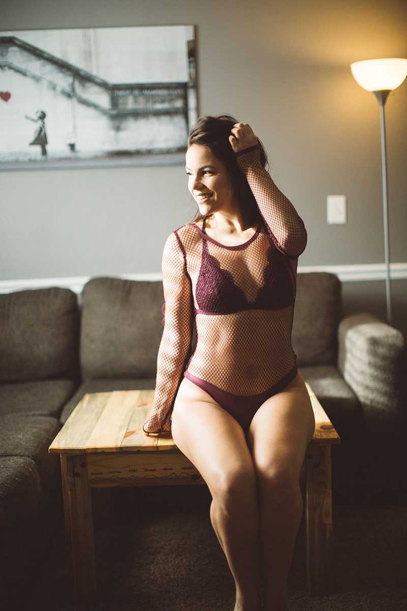 A beautiful young brunette woman poses for some Denver boudoir studio photos at a home studio in Thornton, Colorado sitting on a wood coffee table wearing a maroon bra and underwear set with a red fishnet body suit