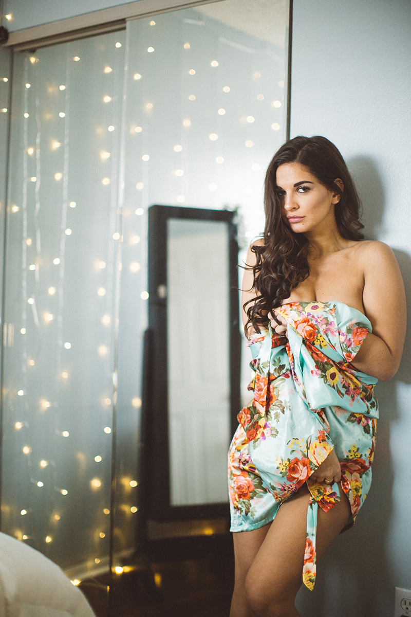 A beautiful young brunette woman poses topless for some Denver boudoir studio photos in a home studio near Thornton, Colorado wearing a blue colorful floral print robe standing in front of a mirror with lights hanging down the walls