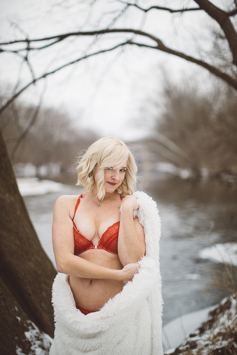 A beautiful blonde woman poses for a Batelle Darby Creek boudoir photography session near Columbus, Ohio wearing a red bra holding a white blanket while standing in a snow covered forest next to a creek