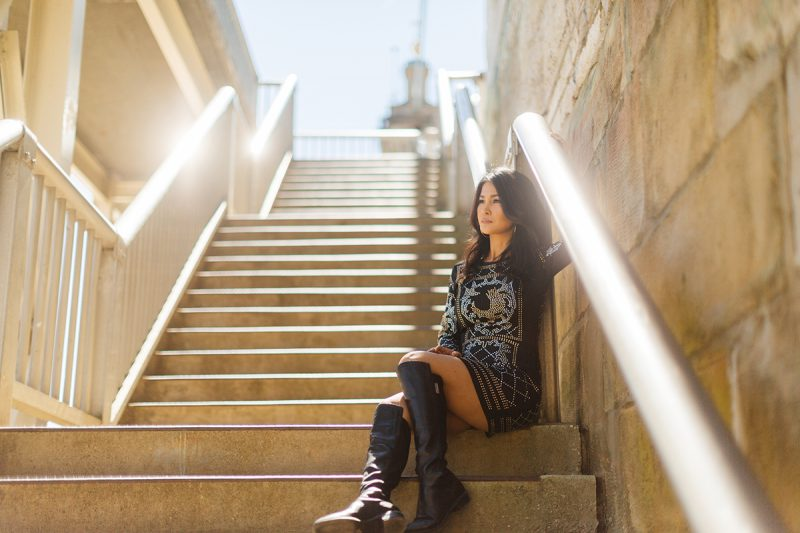 A beautiful brunette woman poses for a Cincinnati urban fashion photography session at the Smale Riverfront Park in Ohio wearing a black dress sitting on steps up to the bridge