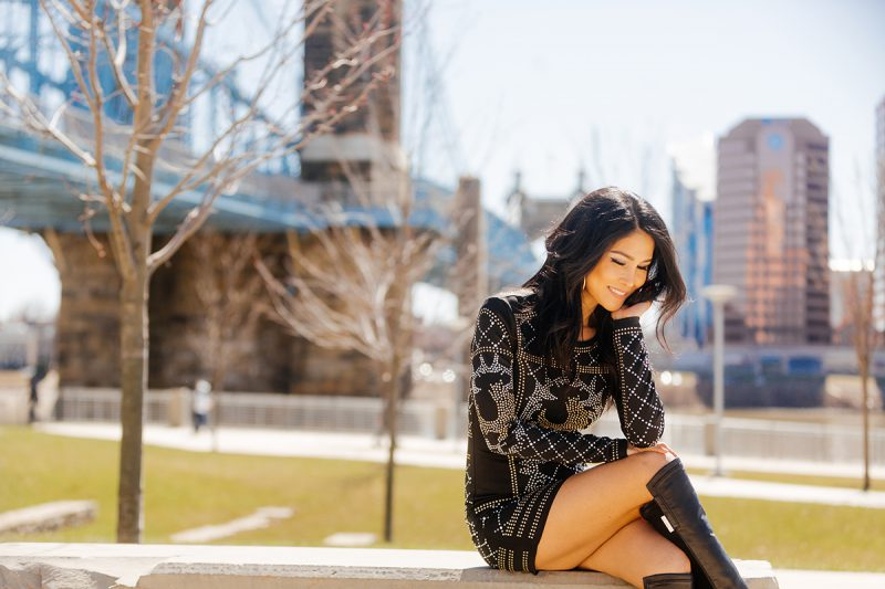 A beautiful brunette woman poses for a Cincinnati urban fashion photography session at the Smale Riverfront Park in Ohio wearing a black dress sitting on a stone bench in front of the blue suspension bridge