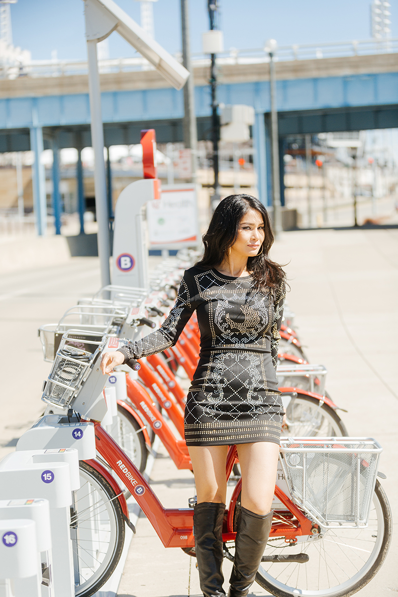 A beautiful brunette woman poses for a Cincinnati urban fashion photography session at the Smale Riverfront Park in Ohio wearing a black dress leaning against some red rental bikes