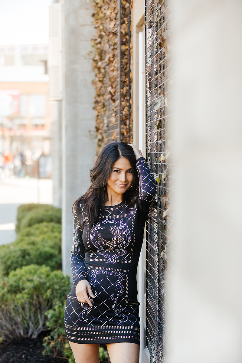 A beautiful brunette woman poses for a Cincinnati urban fashion photography session at the Smale Riverfront Park in Ohio wearing a black dress leaning against a brick building