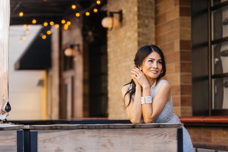 A beautiful brunette woman poses for a Cincinnati urban fashion photography session at the Smale Riverfront Park in Ohio wearing a white dress leaning against some tables at a restaurant