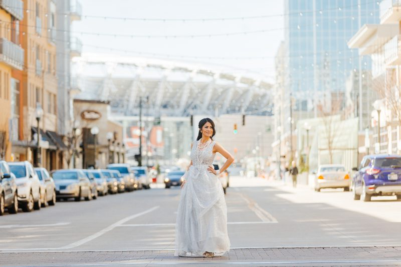 A beautiful brunette woman poses for a Cincinnati urban fashion photography session at the Smale Riverfront Park in Ohio wearing a white dress standing in the middle of the street with the stadium behind her