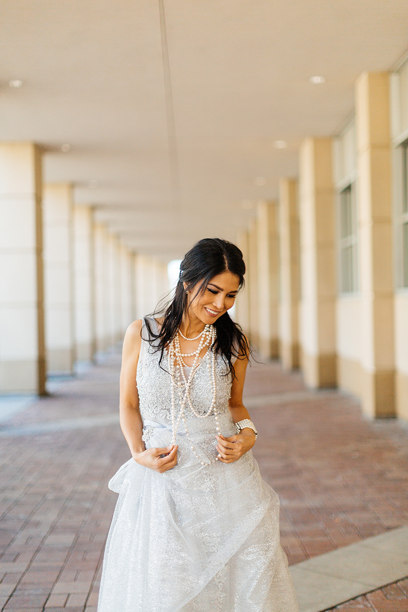 A beautiful brunette woman poses for a Cincinnati urban fashion photography session at the Smale Riverfront Park in Ohio wearing a white dress standing in a row of pillars
