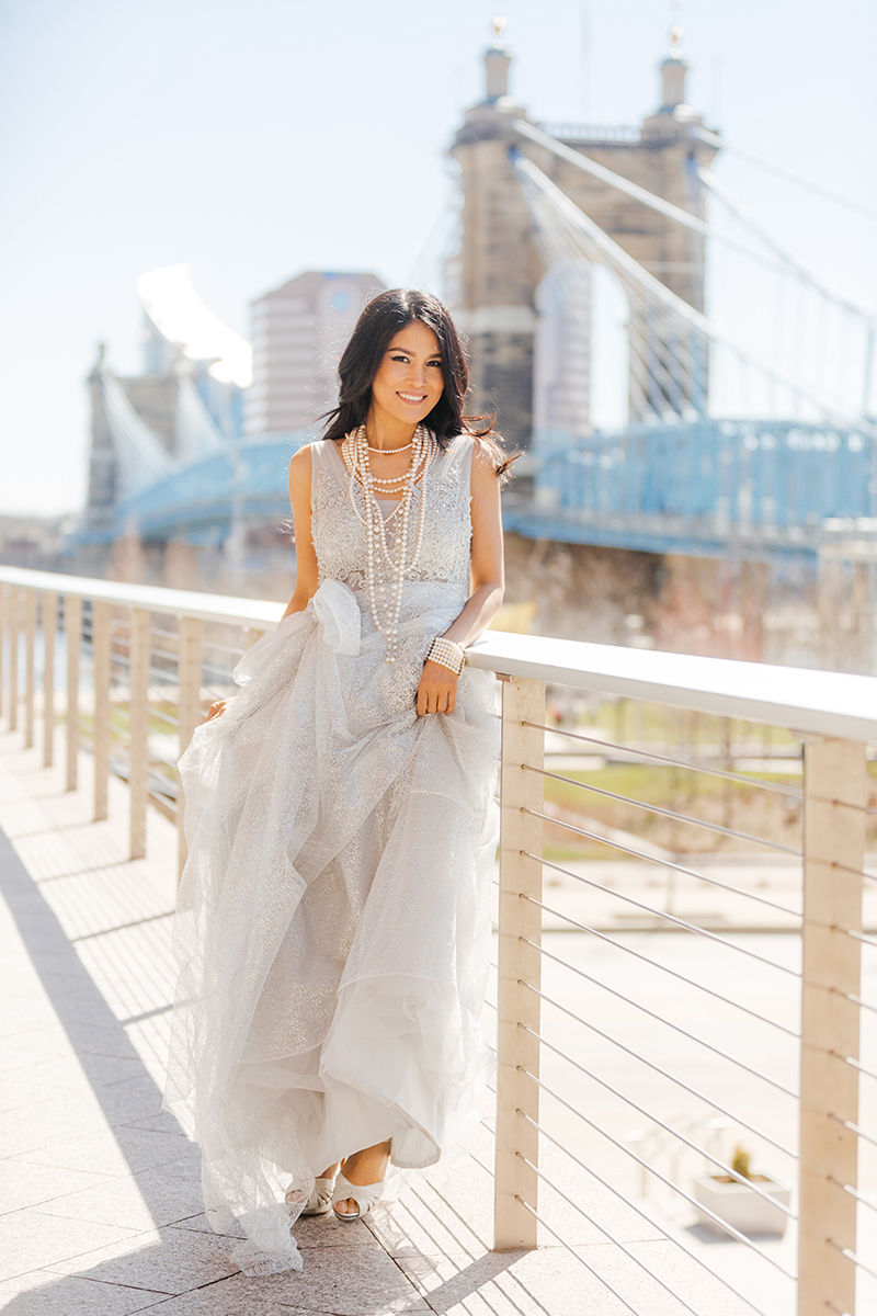 A beautiful brunette woman poses for a Cincinnati urban fashion photography session at the Smale Riverfront Park in Ohio wearing a white dress leaning on a wire fence with the city behind her