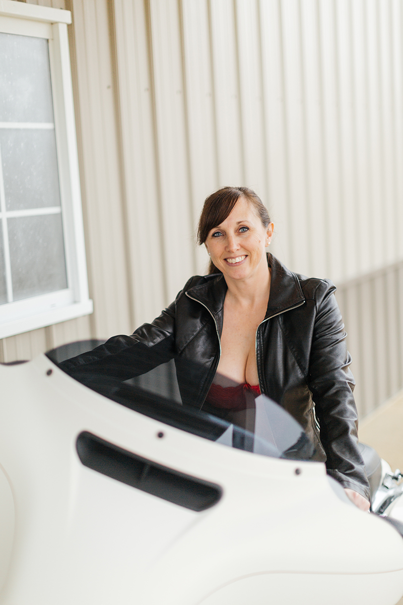 A beautiful mature woman poses for a Harley Davidson boudoir photography session at her home in Marysville, Ohio near Columbus wearing a red bra and underwear set with a black leather jacket and black nylon stockings sitting on a black and white motorcycle outside a garage