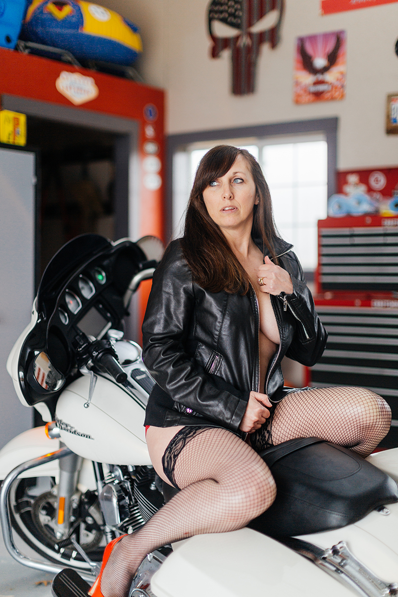 A beautiful mature woman poses topless for a Harley Davidson boudoir photography session at her home in Marysville, Ohio near Columbus wearing red underwear with a black leather jacket and black nylon stockings sitting on a black and white motorcycle in a garage