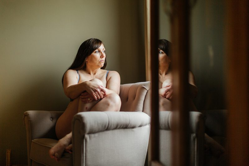 A beautiful mature woman poses for a Harley Davidson boudoir photography session at her home in Marysville, Ohio near Columbus wearing a gray bra and underwear set sitting in a chair next to a wardrobe in front of a window