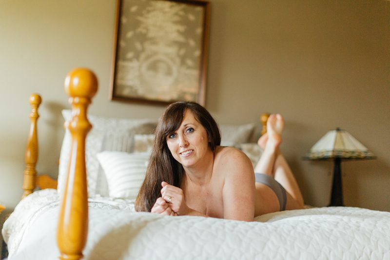 A beautiful mature woman poses topless for a Harley Davidson boudoir photography session at her home in Marysville, Ohio near Columbus wearing gray underwear laying on her bed with a white quilt