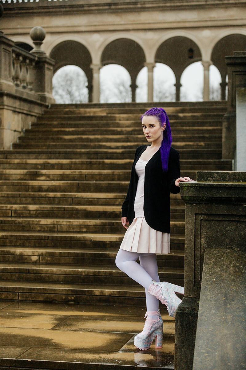 A beautiful young woman with purple hair poses for a Ault Park fashion photography session near Cincinnati, Ohio wearing a tweed jacket a light pink dress, white stockings and large rainbow heels while leaning against a pillar in front of stone steps