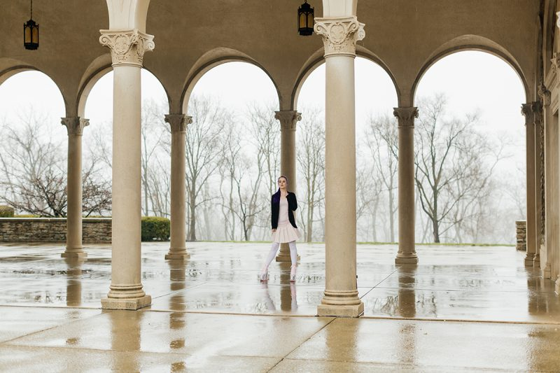 A beautiful young woman with purple hair poses for a Ault Park fashion photography session near Cincinnati, Ohio wearing a tweed jacket a light pink dress, white stockings and large rainbow heels while standing in an archway with pillars around her