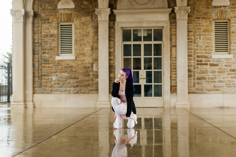 A beautiful young woman with purple hair poses for a Ault Park fashion photography session near Cincinnati, Ohio wearing a tweed jacket a light pink dress, white stockings and large rainbow heels while kneeling in front of a stone building