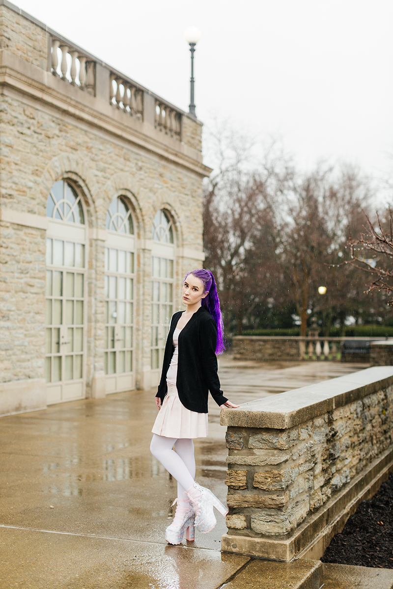 A beautiful young woman with purple hair poses for a Ault Park fashion photography session near Cincinnati, Ohio wearing a tweed jacket a light pink dress, white stockings and large rainbow heels while leaning against a stone wall in front of a stone building
