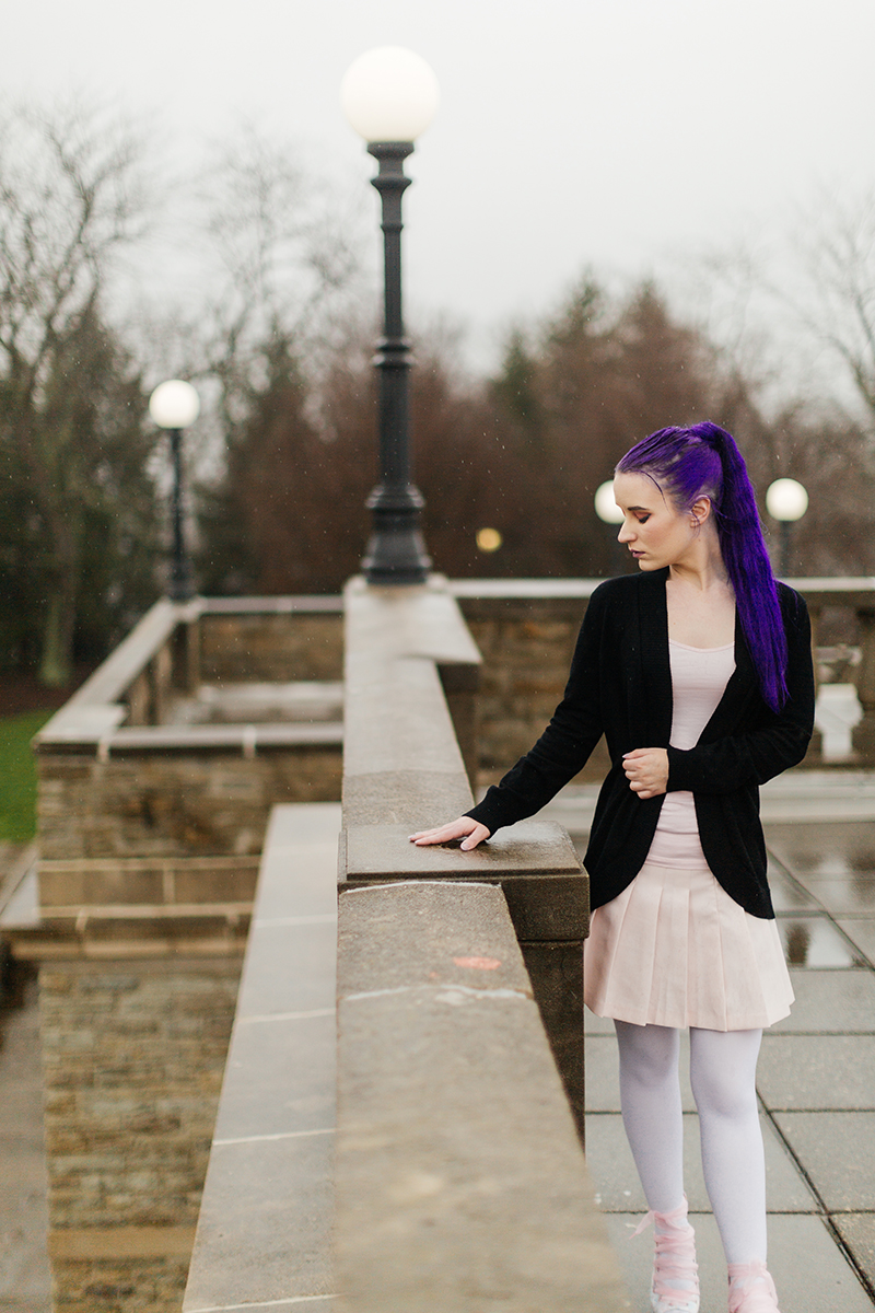 A beautiful young woman with purple hair poses for a Ault Park fashion photography session near Cincinnati, Ohio wearing a tweed jacket a light pink dress, white stockings and large rainbow heels while leaning against a stone wall with light posts behind her