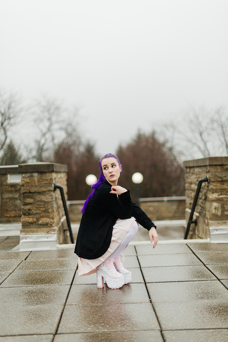 A beautiful young woman with purple hair poses for a Ault Park fashion photography session near Cincinnati, Ohio wearing a tweed jacket a light pink dress, white stockings and large rainbow heels while kneeling on a stone path with light posts behind her