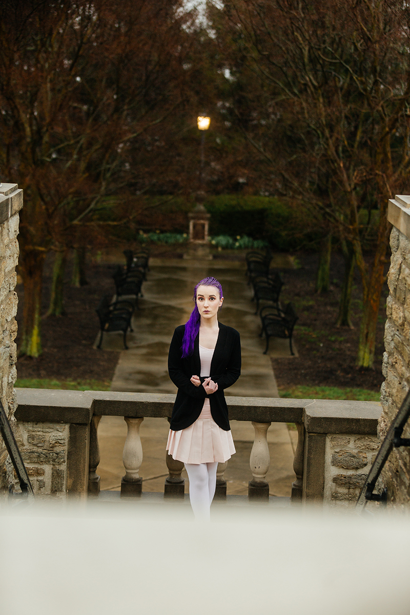 A beautiful young woman with purple hair poses for a Ault Park fashion photography session near Cincinnati, Ohio wearing a tweed jacket a light pink dress, white stockings and large rainbow heels while leaning against a stone wall with a forest walkway behind her