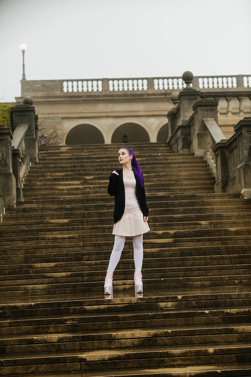 A beautiful young woman with purple hair poses for a Ault Park fashion photography session near Cincinnati, Ohio wearing a tweed jacket a light pink dress, white stockings and large rainbow heels while standing in front of stone steps