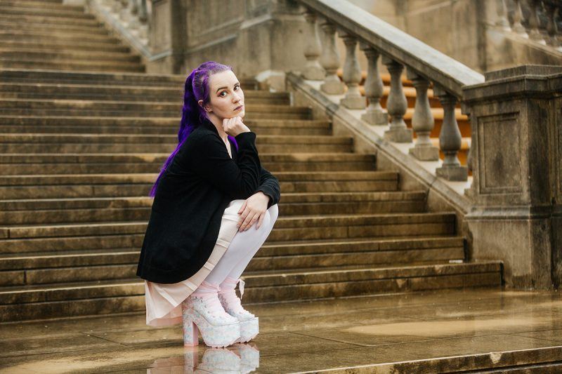 A beautiful young woman with purple hair poses for a Ault Park fashion photography session near Cincinnati, Ohio wearing a tweed jacket a light pink dress, white stockings and large rainbow heels while kneeling in front of stone steps