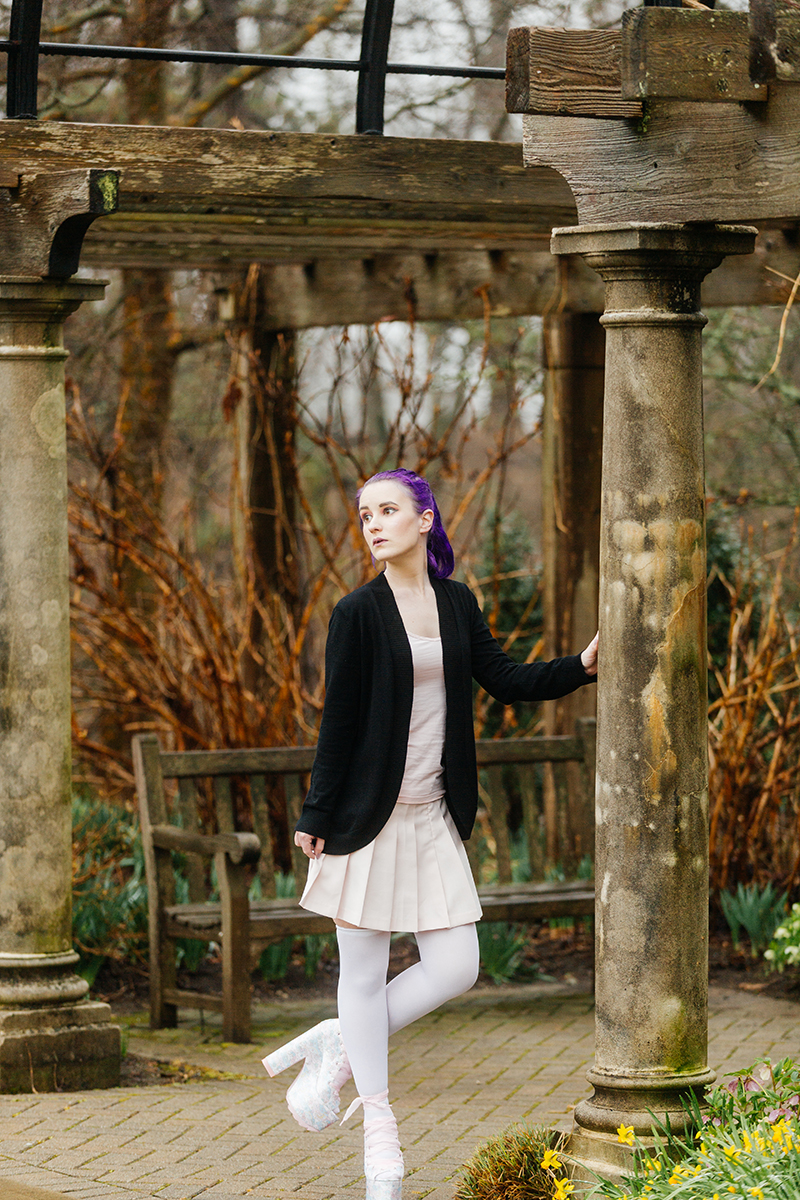 A beautiful young woman with purple hair poses for a Ault Park fashion photography session near Cincinnati, Ohio wearing a tweed jacket a light pink dress, white stockings and large rainbow heels while leaning against a stone pillar in front of a bench