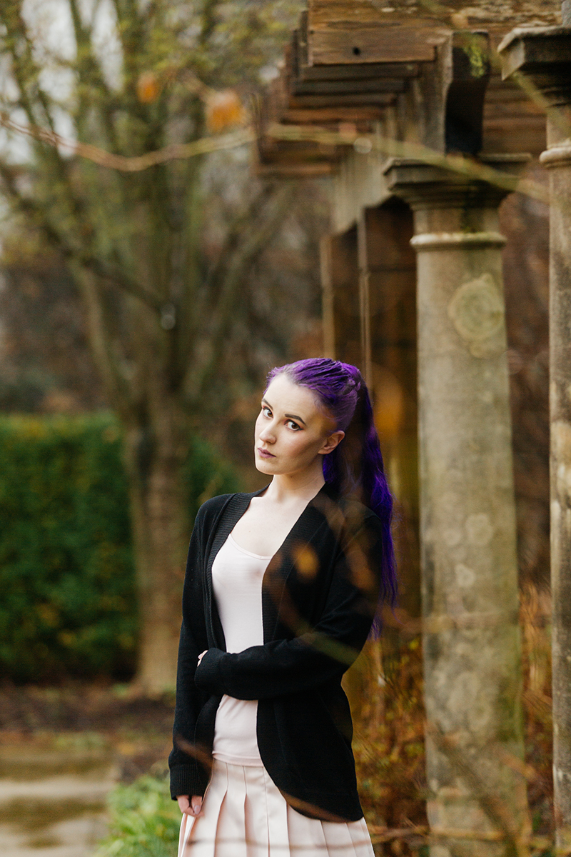 A beautiful young woman with purple hair poses for a Ault Park fashion photography session near Cincinnati, Ohio wearing a tweed jacket a light pink dress, white stockings and large rainbow heels while leaning against a stone pillar