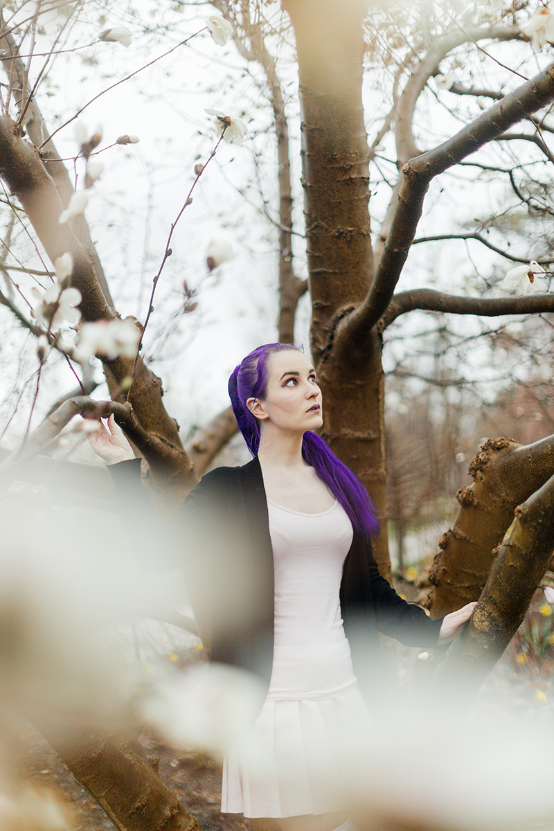 A beautiful young woman with purple hair poses for a Ault Park fashion photography session near Cincinnati, Ohio wearing a tweed jacket a light pink dress, white stockings and large rainbow heels while standing in front of a tree with white blossoms